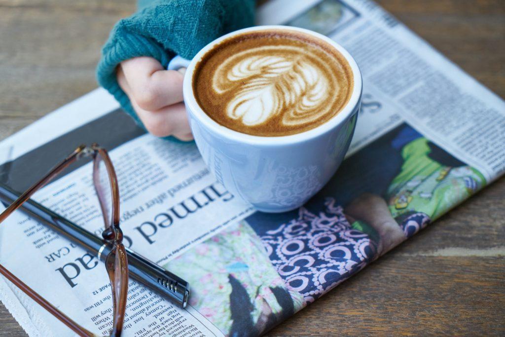 Kubek kawy pity do porannej prasy